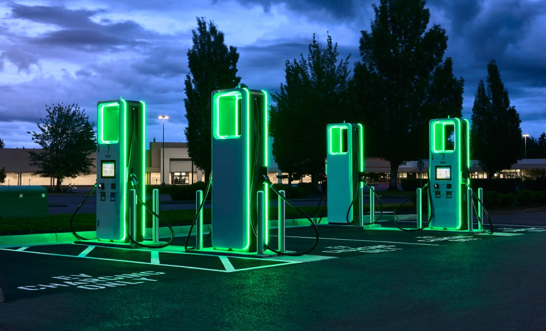 Four electric vehicle charging stations illuminated in green shown in a parking lot at night