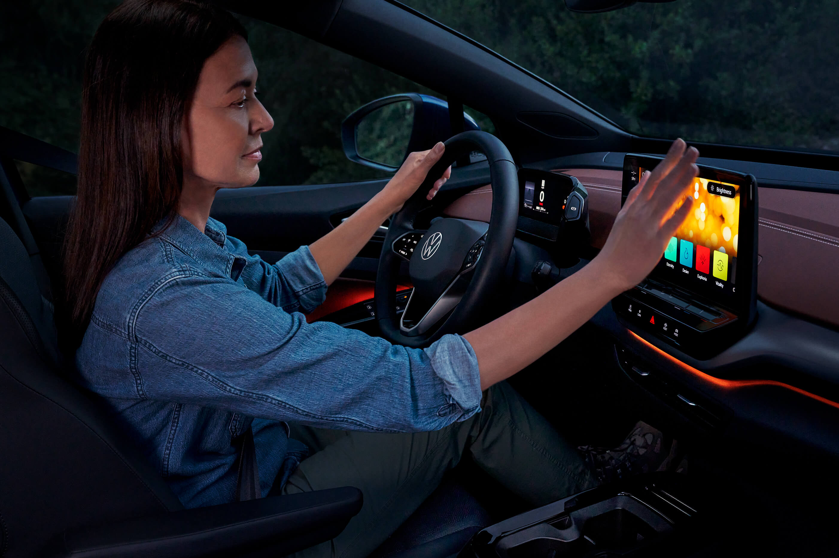 A woman sits in the driver's seat of an ID.4 and adjusts the ambient lighting settings.